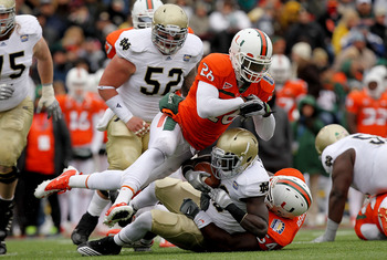 EL PASO, TX - DECEMBER 30:  Running back Cierre Wood #20 of the Notre Dame Fighting Irish is tackled by Ray-Ray Armstrong #26 and Micanor Regis #54 of the Miami Hurricanes at Sun Bowl on December 30, 2010 in El Paso, Texas.  (Photo by Ronald Martinez/Gett