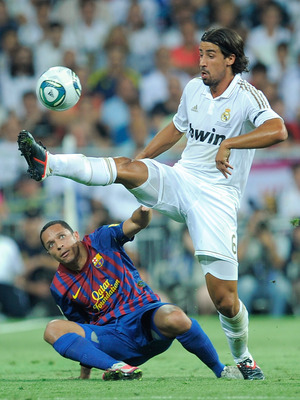 MADRID, SPAIN - AUGUST 14:  Sami Khedira (R) of Real Madrid controls the ball over Adriano of Barcelona during the Super Cup first leg match between Real Madrid and Barcelona at Estadio Santiago Bernabeu on August 14, 2011 in Madrid, Spain.  (Photo by Den
