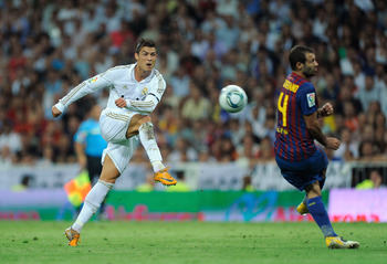 MADRID, SPAIN - AUGUST 14: Cristiano Ronaldo (L) of Real Madrid shoots past  Javer Mascherano of Barcelona during the Super Cup first leg match between Real Madrid and Barcelona at Estadio Santiago Bernabeu on August 14, 2011 in Madrid, Spain.  (Photo by