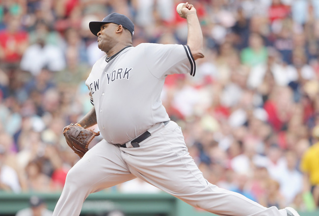 BOSTON, MA - AUGUST 06:  CC Sabathia #52 of the New York Yankees delivers a pitch in the second inning against the Boston Red Sox on August 6, 2011 at Fenway Park in Boston, Massachusetts.  (Photo by Elsa/Getty Images)