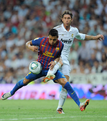 MADRID, SPAIN - AUGUST 14: Alexis Sanchez (L) of Barcelona is tackled by Sergio Ramos of Real Madrid of Barcelona during the Super Cup first leg match between Real Madrid and Barcelona at Estadio Santiago Bernabeu on August 14, 2011 in Madrid, Spain.  (Ph