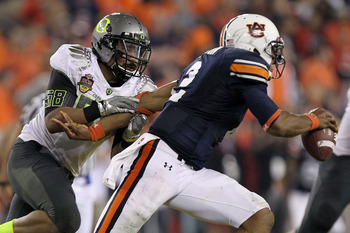 GLENDALE, AZ - JANUARY 10:  Cameron Newton #2 of the Auburn Tigers is chased by Kenny Rowe #58 of the Oregon Ducks during the Tostitos BCS National Championship Game at University of Phoenix Stadium on January 10, 2011 in Glendale, Arizona.  (Photo by Ron