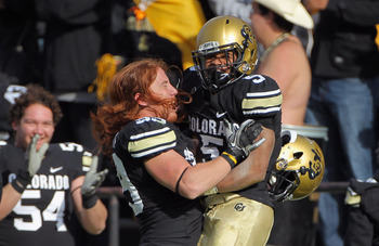 BOULDER, CO - NOVEMBER 20:  Running back Rodney Stewart #5 of the Colorado Buffaloes jumps into the arms of teammate BJ Beatty #59 as he celebrates after throwing an option pass 23 yards to Toney Clemons for a touchdown against the Kansas State Wildcats a