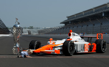 INDIANAPOLIS, IN - MAY 30:  Sebastian, the son of Dan Wheldon of England, driver of the #98 William Rast-Curb/Big Machine Dallara Honda, sits on the yard of bricks next to the Borg Warner Trophy on the day after his father won the IZOD IndyCar Series Indi