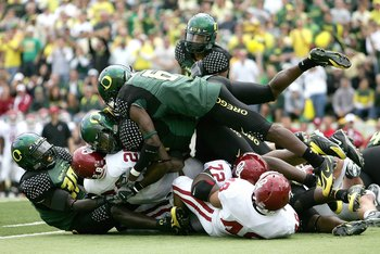 EUGENE, OR - SEPTEMBER 16:  Adrian Peterson #28 of the Oklahoma Sooners is topped by the defense of the Oregon Ducks on September 16, 2006 at Autzen Stadium in Eugene, Oregon.  (Photo by Jonathan Ferrey/Getty Images)