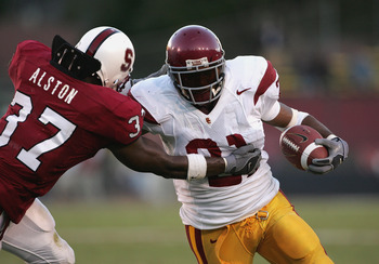 PALO ALTO, CA - SEPTEMBER 25:  LenDale White #21 of the USC Trojans throws a stiff arm against Jon Alston #37 of the Stanford Cardinals during the game on September 25, 2004 at Stanford Stadium in Palo Alto, California.  USC defeated Stanford 31-28. (Phot