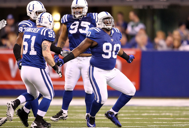 INDIANAPOLIS, IN - JANUARY 08:  Dan Muir #90 of the Indianapolis Colts celebrates with Pat Angerer #51 and Fili Moala #95 after he sacked quarterback Mark Sanchez #6 of the New York Jets in the first quarter during their 2011 AFC wild card playoff game at
