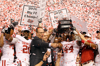 ARLINGTON, TX - DECEMBER 04:  Big 12 Commissioner Dan Bebee presents defensive end Jeremy Beal #44 of the Oklahoma Sooners with the Big 12 Championship Trophy after the Sooners beat the Nebraska Cornhuskers 23-20 at Cowboys Stadium on December 4, 2010 in