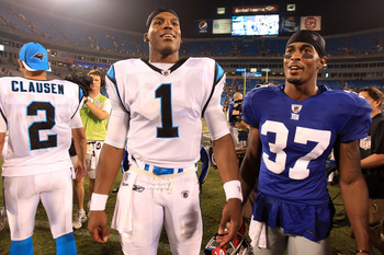 CHARLOTTE, NC - AUGUST 13:  Michael Coe #37 of the New York Giants stands with Cam Newton #1 of the Carolina Panthers after their preseason game at Bank of America Stadium on August 13, 2011 in Charlotte, North Carolina.  (Photo by Streeter Lecka/Getty Im