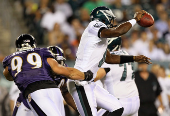 PHILADELPHIA, PA - AUGUST 11:  Vince Young #9 of the Philadelphia Eagles eludes a tackle by Paul Kruger #99 of the Baltimore Ravens during their preseason game on August 11, 2011 at Lincoln Financial Field in Philadelphia, Pennsylvania.  (Photo by Jim McI