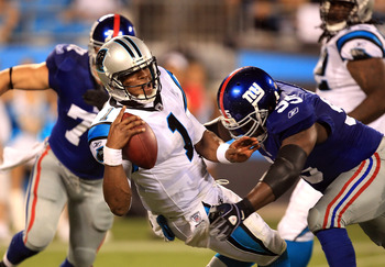 CHARLOTTE, NC - AUGUST 13:  Rocky Bernard #95 of the New York Giants tackles Cam Newton #1 of the Carolina Panthers during their preseason game at Bank of America Stadium on August 13, 2011 in Charlotte, North Carolina.  (Photo by Streeter Lecka/Getty Ima