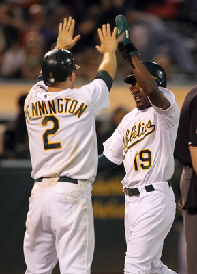 OAKLAND, CA - AUGUST 16:  Jemile Weeks #19 and Cliff Pennington #2 of the Oakland Athletics congratulate one another after they both scored on a double by Coco Crisp #4 of the Oakland Athletics in the seventh inning of their game against the Baltimore Ori