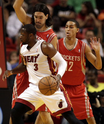 MIAMI, FL - MARCH 27:  Guard Dwyane Wade of the Miami Heat drives against gurad Kevin Martin #12 and forward Luis Scola #4 of the Houston Rockets at American Airlines Arena on March 27, 2011 in Miami, Florida. NOTE TO USER: User expressly acknowledges and