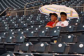 PITTSBURGH - JULY 18:  Two young Cincinnati Reds fans sit under an umbrella during the rain before a game between the Pittsburgh Pirates and the Cincinnati Reds on July 18, 2011 at PNC Park in Pittsburgh, Pennsylvania.  (Photo by Jared Wickerham/Getty Ima