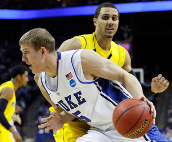 CHARLOTTE, NC - MARCH 20:  Mason Plumlee #5 of the Duke Blue Devils drives on Jordan Morgan #52 of the Michigan Wolverines in the first half during the third round of the 2011 NCAA men's basketball tournament at Time Warner Cable Arena on March 20, 2011 i