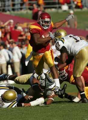 LOS ANGELES, CA - DECEMBER 03:  Reggie Bush #5 of the USC Trojans rushes the ball past the UCLA Bruins defense December 3, 2005 at the Los Angeles Memorial Coliseum in Los Angeles, California.  (Photo by Stephen Dunn/Getty Images)