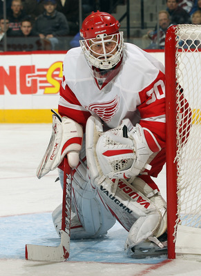 DENVER - DECEMBER 27:  Goalie Chris Osgood #30 of the Detroit Red Wings defends the goal against the Colorado Avalanche at the Pepsi Center on December 27, 2010 in Denver, Colorado. Osgood earned his 400th win and collected 46 saves as the Red Wings defea