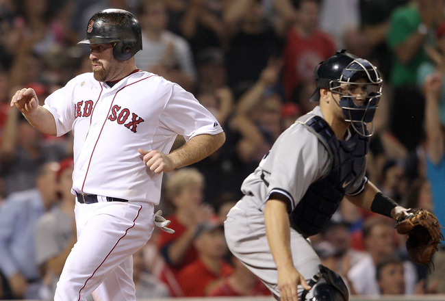 BOSTON, MA - AUGUST 07:  Kevin Youkilis #20 of the Boston Red Sox scores a run off a hit by Marco Scutaro in the second inning as Russell Martin #55 of the New York Yankees defends on August 7, 2011 at Fenway Park in Boston, Massachusetts.  (Photo by Elsa