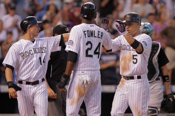 DENVER, CO - AUGUST 17:  Carlos Gonzalez #5 of the Colorado Rockies is welcomed home by Mark Ellis #14 and Dexter Fowler #24 of the Rockies who scored on his three run home run off of starting pitcher Ricky Nolasco of the Florida Marlins to give the Rocki