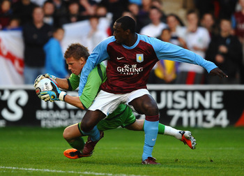 WALSALL, ENGLAND - JULY 21: Emile Heskey of Aston Villa battles with James Walker of Walsall during a Pre Season Friendly between Walsall and Aston Villa at Banks' Stadium on July 21, 2011 in Walsall, England.  (Photo by Laurence Griffiths/Getty Images)