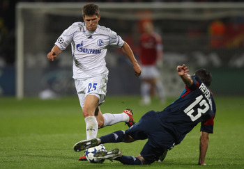 LYON, FRANCE - SEPTEMBER 14:  Klaas-Jan Huntelaar of Schalke is tackled by Anthony Reveillere during the UEFA Champions League Group B match between Olympique Lyonnais and FC Schalke 04 at the Stade de Gerland on September 14, 2010 in Lyon, France.  (Phot