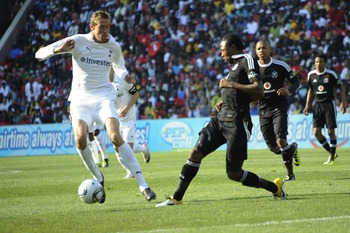 JOHANNESBURG, SOUTH AFRICA - JULY 23:  Peter Crouch of Tottenham and Siyabonga Sangweni of Piratesin action during the 2011 Vodacom Challenge final match between Orlando Pirates and Tottenham Hotspur at Coca Cola Stadium on July 23, 2011 in Johannesburg,