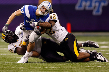 NEW ORLEANS - DECEMBER 20:  Shane Blissard #83 of the Middle Tennessee Blue Raiders is tackled by Cordarro Law #49 and Korey Williams #42 of the Southern Miss Golden Eagles  during the R+L Carriers New Orleans Bowl at the Louisiana Superdome on December 2