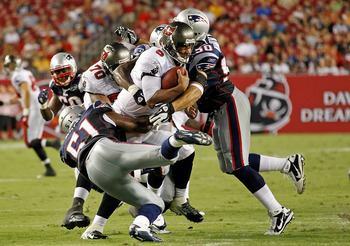 TAMPA, FL - AUGUST 18:  Quarterback Josh Freeman #5 of the Tampa Bay Buccaneers is sacked by Rob Ninkovich #50 (right) and Jerod Mayo #51 of the New England Patriots during a preseason game at Raymond James Stadium on August 18, 2011 in Tampa, Florida.  (