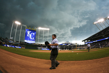 KANSAS CITY, MO - AUGUST 07: Plate umpire Rob Drake #30 leaves the playing field as a game between the Detroit Tigers and Kansas City Royals is delayed by rain in the sixth inning at Kauffman Stadium on August 7, 2011 in Kansas City, Missouri.  (Photo by