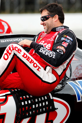 LONG POND, PA - AUGUST 06: Tony Stewart, driver of the #14 Office Depot/Mobil 1 Chevrolet, climbs into his car on the grid during qualifying for the NASCAR Sprint Cup Series Good Sam RV Insurance 500 at Pocono Raceway on August 6, 2011 in Long Pond, Penns
