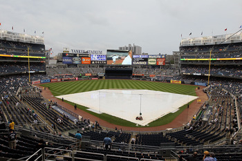 NEW YORK, NY - JULY 25:  A tarp is seen on the field as the game between the New York Yankees and the Seattle Mariners is delayed by rain on July 25, 2011 at Yankee Stadium in the Bronx borough of New York City.  (Photo by Jim McIsaac/Getty Images)