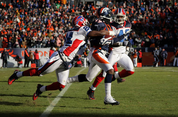 DENVER - DECEMBER 21:  Wide receiver Eddie Royal #19 of the Denver Broncos rushes 71 yards on an end around and is tackled by cornerback Terrence McGee #24 of the Buffalo Bills as safety Bryan Scott #43 of the Bills follows the play during NFL action at I