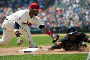 CLEVELAND, OH - JULY 10:  First baseman Carlos Santana #41 of the Cleveland Indians tries to pick off Rajai Davis #11 of the Toronto Blue Jays during the sixth inning at Progressive Field on July 10, 2011 in Cleveland, Ohio. (Photo by Jason Miller/Getty I