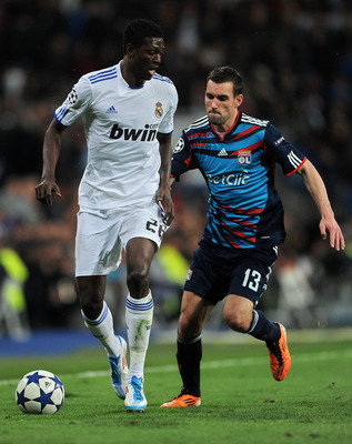 MADRID, SPAIN - MARCH 16:  Emmanuel Adebayor (L) of Real Madrid duels for the ball with Anthony Reveillere of Lyon during the UEFA Champions League round of 16 second leg match between Real Madrid and Lyon at Estadio Santiago Bernabeu on March 16, 2011 in