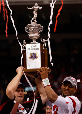 Coach Kyle Whittingham and QB Brian Johnson hoist the 2009 Sugar Bowl Champions trophy after they handily beat highly favored Alabama, 31-17. The Utes began the game with three straight scoring drives and led 21-0 early.