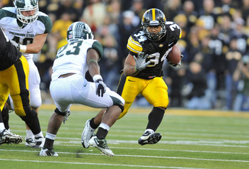IOWA CITY, IA - OCTOBER 30- Running back Marcus Coker #34 of the University of Iowa Hawkeyes runs past safety Jairus Jones #23 of the Michigan State Spartans during the second half of play at Kinnick Stadium on October 30, 2010 in Iowa City, Iowa. Iowa wo