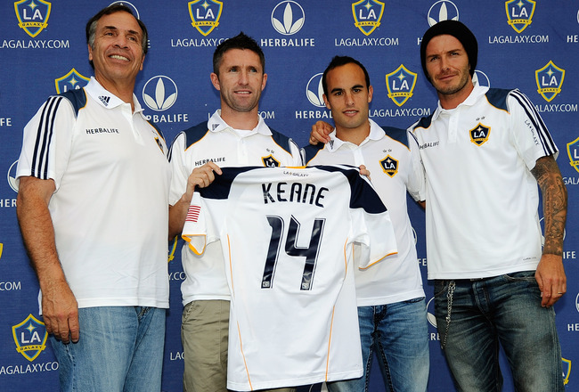 CARSON, CA - AUGUST 19:  Newly acquired Los Angeles Galaxy forward Robbie Keane#14 holds his jersey as he poses with teammates David Beckham #23, Landon Donovan #10 and head coach Bruce Arena (R) after a news conference at The Home Depot Center on August