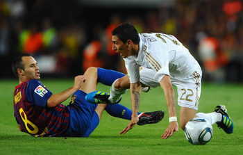 BARCELONA, SPAIN - AUGUST 17: Andres Iniesta of Barcelona battles with Angel di Maria of Real Madrid during the Super Cup second leg match between Barcelona and Real Madrid at Nou Camp on August 17, 2011 in Barcelona, Spain.  (Photo by Laurence Griffiths/