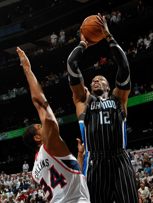 ATLANTA, GA - APRIL 24:  Dwight Howard #12 of the Orlando Magic shoots over Jason Collins #34 of the Atlanta Hawks during Game Four of the Eastern Conference Quarterfinals in the 2011 NBA Playoffs at Philips Arena on April 24, 2011 in Atlanta, Georgia.  N