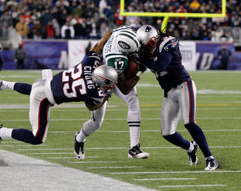 FOXBORO, MA - DECEMBER 06:  Braylon Edwards #17 of the New York Jets is hit as he runs for yards after the catch by Patrick Chung #25 and Brandon Meriweather #31 of the New England Patriots at Gillette Stadium on December 6, 2010 in Foxboro, Massachusetts