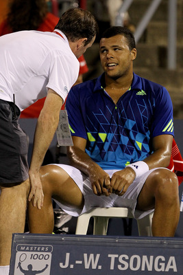 MONTREAL, QC - AUGUST 13:  Jo-Wilfried Tsonga of France consults ATP trainer Paul Ness in the second set against Novak Djokovic of Serbia during the Rogers Cup at Uniprix Stadium on August 13, 2011 in Montreal, Canada.  (Photo by Matthew Stockman/Getty Im