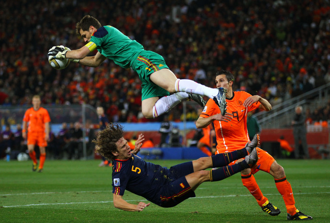 JOHANNESBURG, SOUTH AFRICA - JULY 11:  Iker Casillas of Spain catches the ball ahead of Robin Van Persie of the Netherlands as Carles Puyol of Spain falls to the ground during the 2010 FIFA World Cup South Africa Final match between Netherlands and Spain