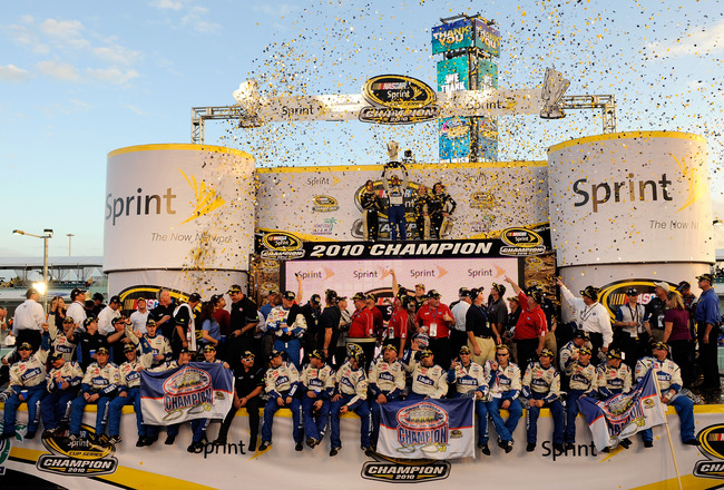 HOMESTEAD, FL - NOVEMBER 21:  Jimmie Johnson, driver of the #48 Lowe's Chevrolet, celebrates by hoisting the trophy after finishing in second place in the Ford 400 to clinch his fifth consecutive NASCAR Sprint Cup championship at Homestead-Miami Speedway