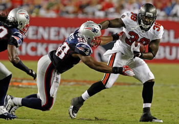 TAMPA, FL - AUGUST 18:  Running back Allen Bradford #38 of the Tampa Bay Buccaneers breaks the tackle of defender Tracy White #58 of the New England Patriots during a preseason game at Raymond James Stadium on August 18, 2011 in Tampa, Florida.  (Photo by
