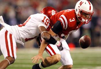 ARLINGTON, TX - DECEMBER 04:  Quarterback Taylor Martinez #3 of the Nebraska Cornhuskers fumbles the ball under pressure from defensive back Demontre Hurst #19 of the Oklahoma Sooners at Cowboys Stadium on December 4, 2010 in Arlington, Texas. The Sooners