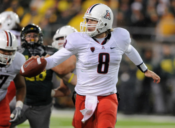 EUGENE, OR - NOVEMBER 26: Quarterback Nick Foles #8 of the Arizona Wildcats looks for someone to flip the ball to in the fourth quarter of the game at against the Oregon Ducks at Autzen Stadium on November 26, 2010 in Eugene, Oregon. The Ducks won the gam