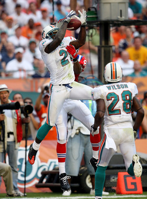 MIAMI - DECEMBER 06:  Cornerback Vontae Davis #21 of the Miami Dolphins intercepts a pass in the end-zone in front of wide receiver Randy Moss #81 of the New England Patriots at Land Shark Stadium on December 6, 2009 in Miami, Florida. The Dolphins defeat