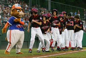 SOUTH WILLIAMSPORT, PA - AUGUST 23:  Members of the Northwest team from Oregon dance with the Little League mascot 'Dugout' before they play the Great Lakes team from Illinois during the United States Semifinal game in the Little League World Series on Au