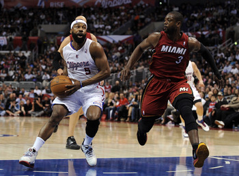 LOS ANGELES, CA - JANUARY 12:  Baron Davis #5 of the Los Angeles Clippers dribbles around Dwyane Wade #3 of the Miami Heat at Staples Center on January 12, 2011 in Los Angeles, California.  NOTE TO USER: User expressly acknowledges and agrees that, by dow