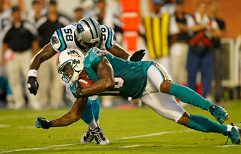 MIAMI GARDENS, FL - AUGUST 19:  Brandon Marshall #19 of the Miami Dolphins is tackled by Thomas Davis #58 of the Carolina Panthers during a Preseason NFL game  at Sun Life Stadium on August 19, 2011 in Miami Gardens, Florida.  (Photo by Mike Ehrmann/Getty
